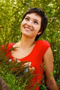 Happy Woman wearing red top surrounded by green plants and flowers