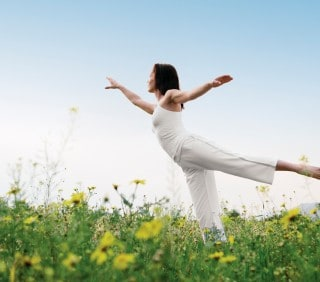 Woman Practicing Yoga in a Field of Flowers