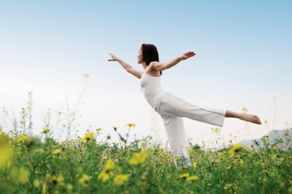 Woman standing on one leg doing a yoga pose in a field with yellow flowers
