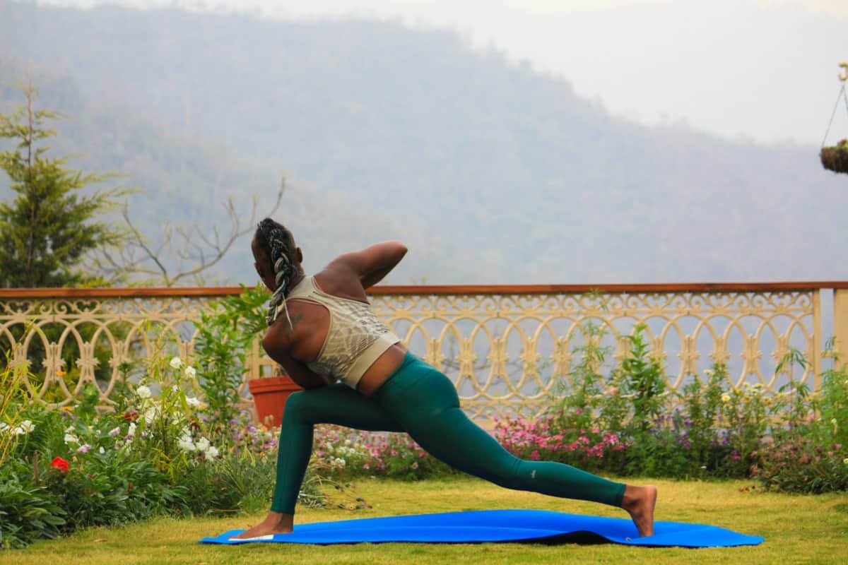 Woman doing balanced yoga pose outside.