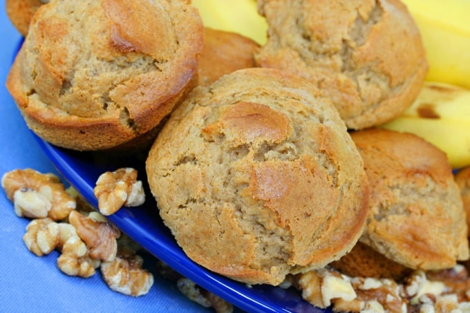 Banana walnut muffins on a blue plate with walnuts and bananas