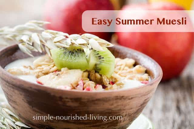 Muesli in a wooden bowl topped with sliced kiwifruit and chopped apple with two apples in the background