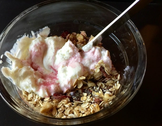 Mixing together muesli with yogurt and blueberries in a clear bowl