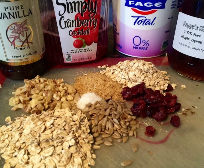 Summer muesli ingredients - old-fashioned oats, chopped walnuts, sunflower seeds, wheatgerm and chopped cranberries - on a cutting board with pure vanilla extract, cranberry juice, Fage non-fat Greek yogurt and pure maple syrup in the background