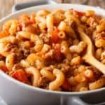 American Chop Suey (Hamburger Goulash with Elbow Macaroni), ground beef, tomatoes, tomato sauce and spices close-up in a white serving dish.