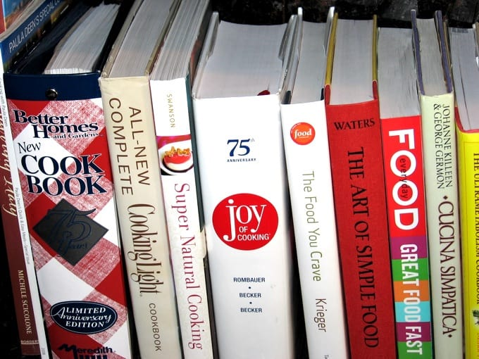 Cookbooks on a shelf featuring Joy of Cooking