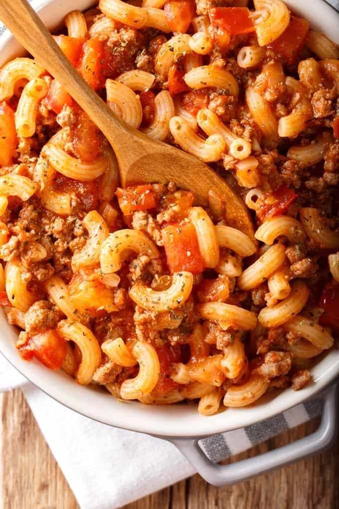 Hamburger Macaroni Goulash with tomatoes in serving dish with wooden spoon.