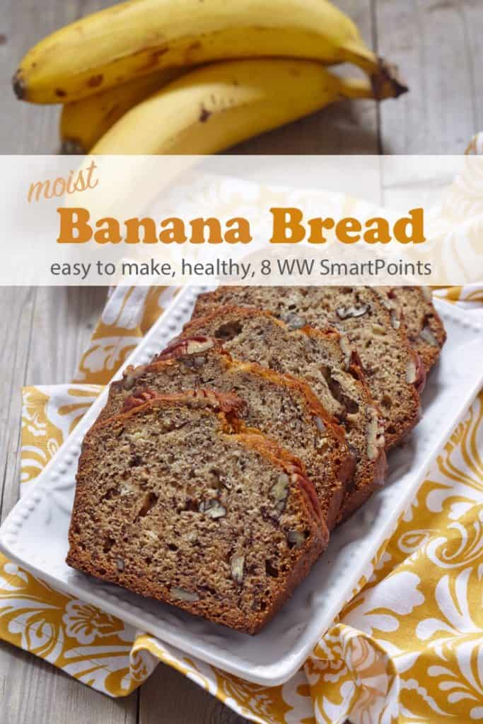 Sliced banana bread with walnuts on a white serving plate with a yellow napkin and bunch of bananas in the background
