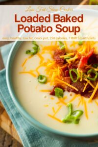 Loaded baked potato soup topped with crispy chopped bacon, sliced green onion and cheddar cheese in blue bowl.