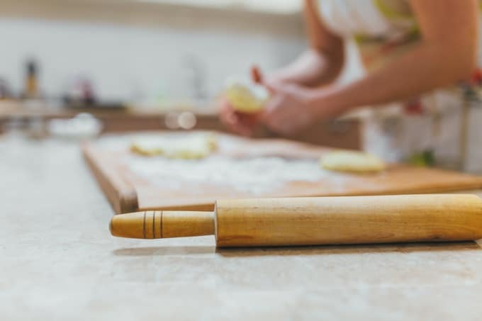 Baking preparation, top view on wooden board or table with wood rolling pin.