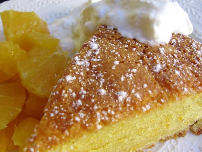 Wedge of orange-scented olive oil cake with oranges and whipped cream.
