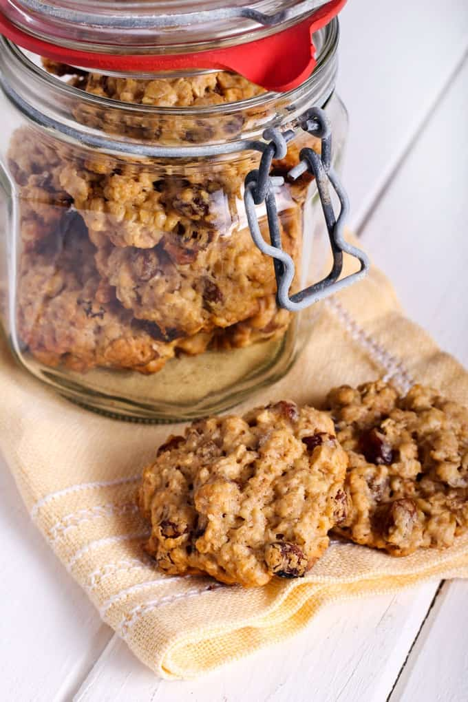 Applesauce Oatmeal Cookies in a glass jar with two cookies on a yellow napkin
