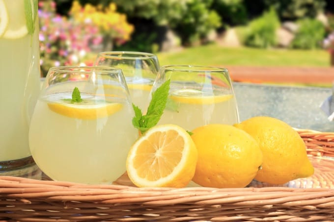 Basket with 3 glasses of fresh lemonade with lemons on the side
