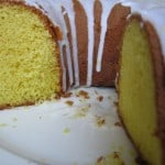 close up front view lemon supreme pound cake with glaze on white plate
