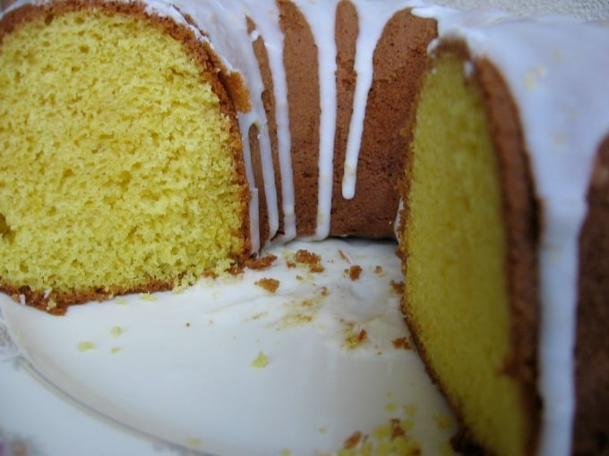 Freshly cut lemon supreme pound cake with icing on white cake plate.