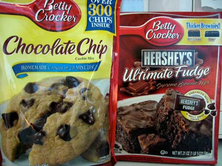 Package of Betty Crocker Chocolate Chip Cookie Mix Next To Box of Betty Crocker Hershey's Ultimate Fudge Supreme Brownie Mix