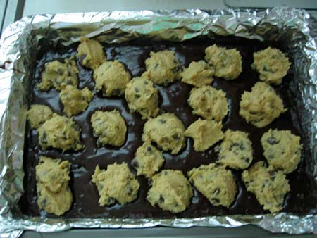 Overhead Shot with Pan of Unbaked Chocolate Brownies Topped with Scoops of Chocolate Chip Cookie Dough