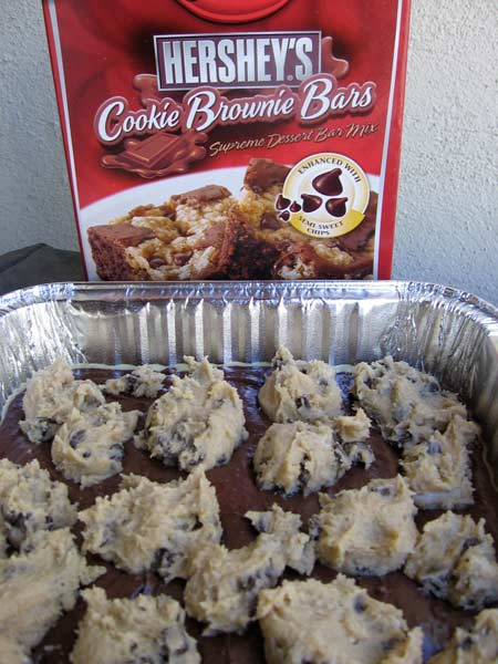Uncooked Pan of Cookie Brownie Bars with Red Box of Betty Crocker Hershey's Cookie Brownie Bars in the Background