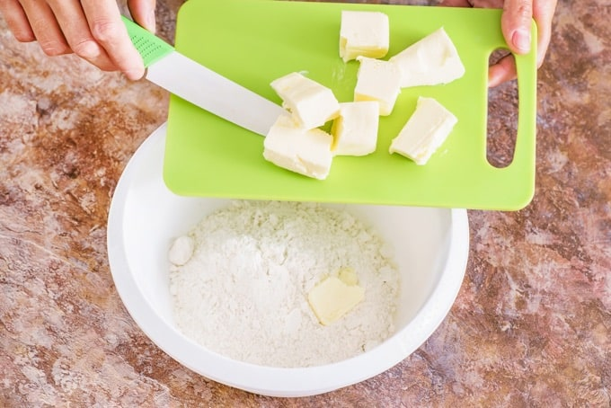 Adding butter slices from a green cutting board into a white bowl with flour