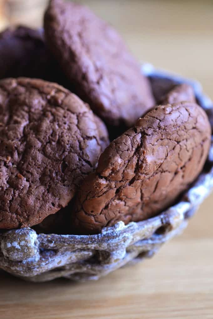 A bunch of chocolate cookies in a ceramic bowl on a wood table