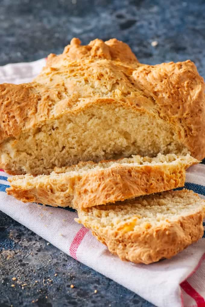 Traditional Irish soda bread on a red and blue striped towel on a blue stone background