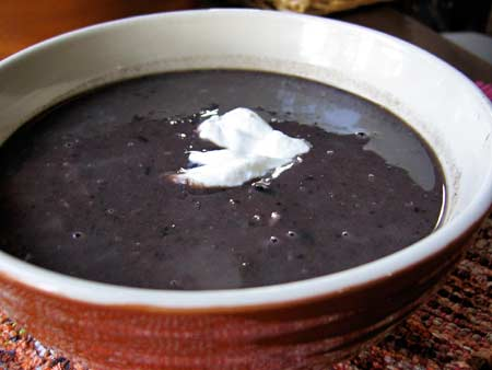 Bowl of Black Bean Soup topped with yogurt