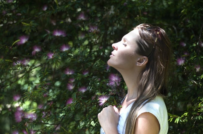 Woman with eyes closed and head tipped back taking a deep breath
