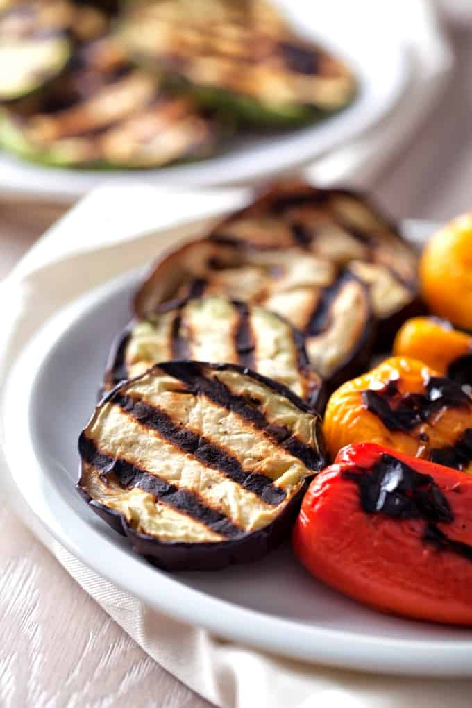 Slices of grilled eggplant, red and yellow peppers with grill marks on white plate.