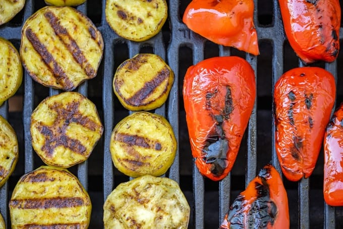 Slices of summer squash and red bell peppers on grill with grill marks.