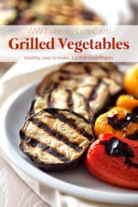 Grilled eggplant with red and yellow peppers on white serving platter.