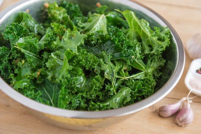 Fresh Kale in a Bowl with cloves of garlic