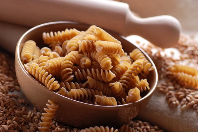 Uncooked brown rice fusilli pasta in bowl
