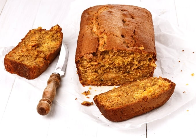 Pumpkin bread loaf with two slices over white wooden background