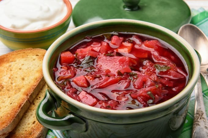 Winter Borscht in a green bowl with a spoon and toasted bread