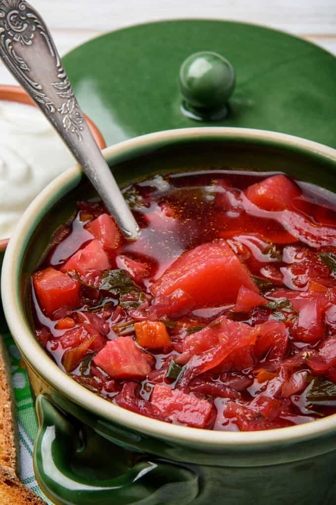 Winter Borscht Soup in a green crock with a spoon
