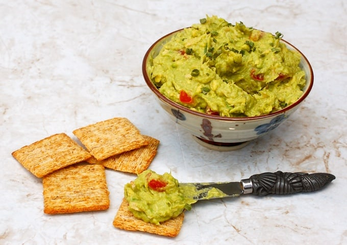 Smear of guacamole on a Triscuit cracker with more crackers near bowl with homemade guacample