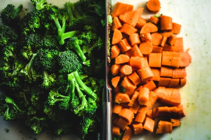 Fresh chopped broccoli florets and carrots on a cutting board