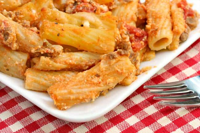 Close UP of Baked Ziti with Cottage Cheese on White Plate Red Checked Tablecloth