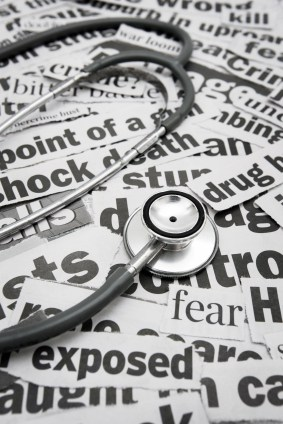 Newspaper headline clippings with a medical stethoscope sitting on top