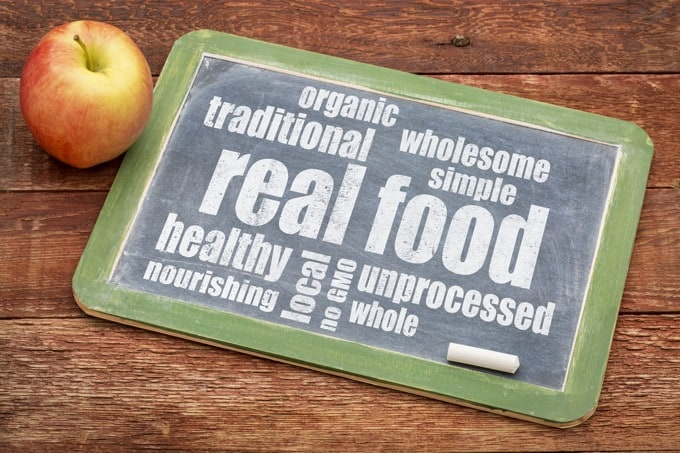 Real Food Word Cloud written a Blackboard next to a Fresh-Picked Apple on a Wood Table