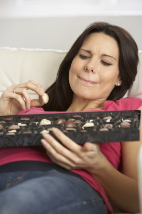 Woman with Brown Hair Lying on a Couch Holding a Box of Chocolates on her Lap