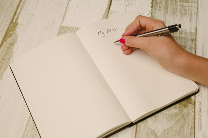 hand holding pen writing in a planner
