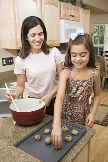 Mom and daughter placing cookie dough balls on baking sheet.