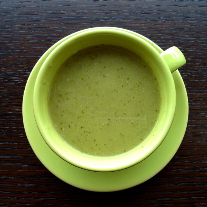 Curried green zucchini soup in green mug on dark wood table.