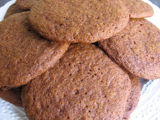 Molasses cookies stacked on a white plate
