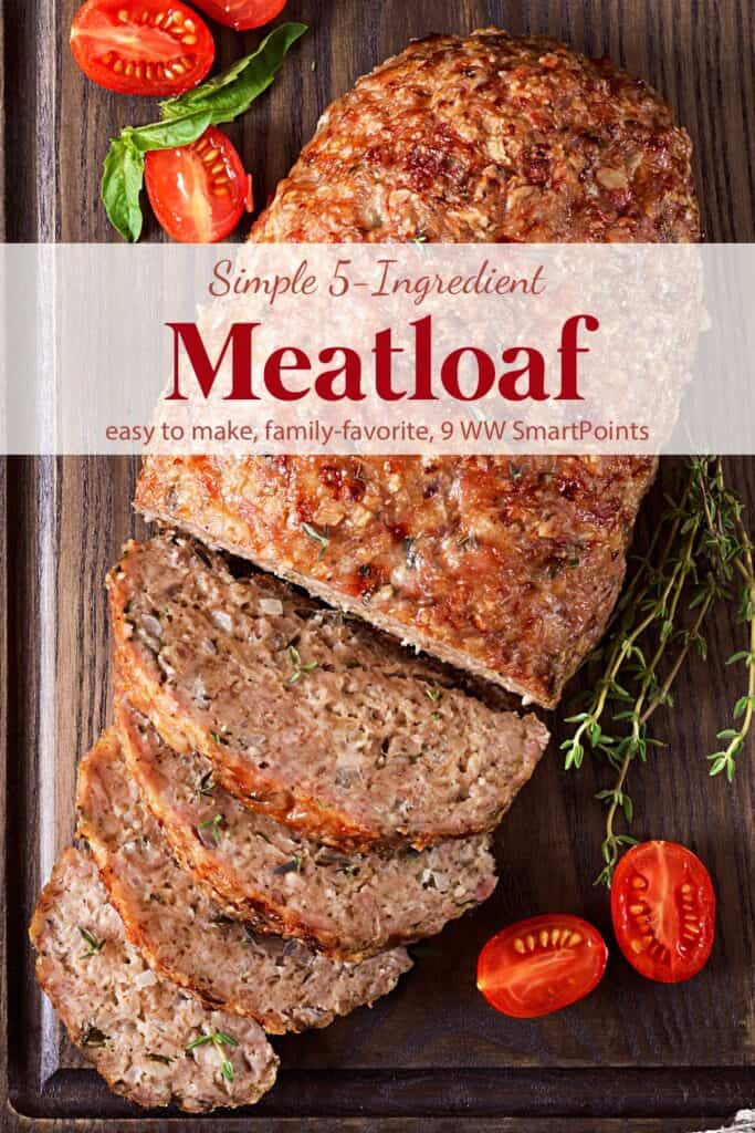Meatloaf with slices on wood cutting board with fresh herbs and grape tomatoes.