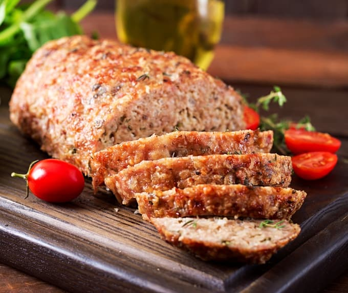 Whole meatloaf with slices on a cutting board with fresh tomatoes and herbs