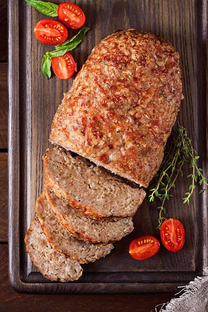 Sliced meatloaf on a cutting board with fresh tomatoes and herbs