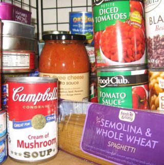 Well-stocked pantry shelf with cans and jars of food and a package of dry pasta