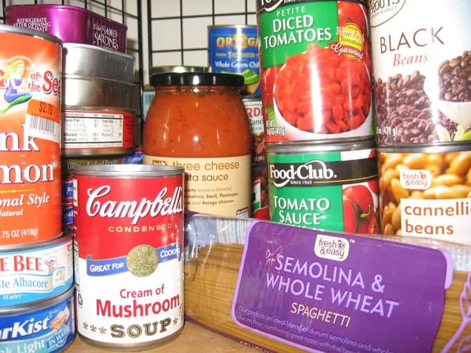 Well-stocked pantry shelf with cans and jars of food and a package of dry pasta.